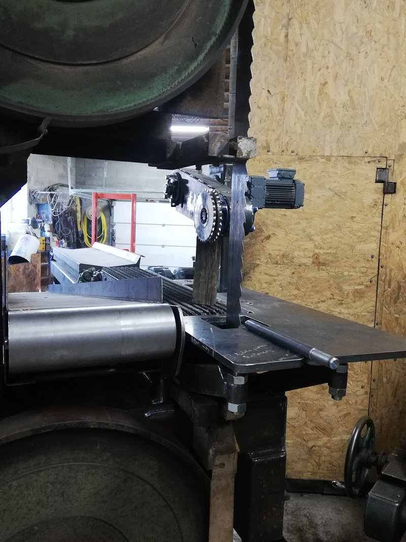 ensemble de sciage refendeur automatique pour piquet ou échala sur scie à ruban avec presseur haut , entraîneur chaîne basse, éjecteur , tapis retour vers opérateur et tapis d'évacuation des déchets